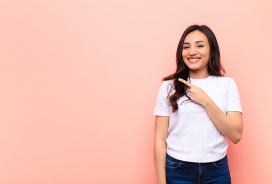 young latin pretty woman smiling cheerfully, feeling happy and pointing to the side and upwards, showing object in copy space against flat wall