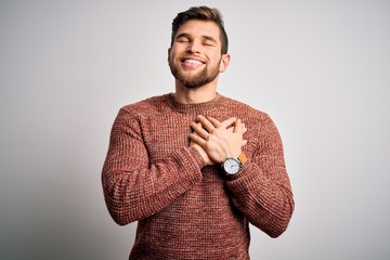 Young blond man with beard and blue eyes wearing casual sweater over white background smiling with...