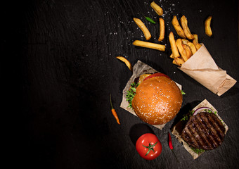 Top view of home made tasty burgers onblack stone table.