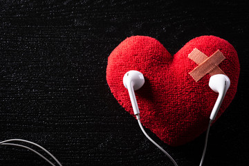 First aid band cushioned plaster strip medical patch glued on red heart with earphone listen to music on wooden background. Heart broken, Love and Valentines day concept.