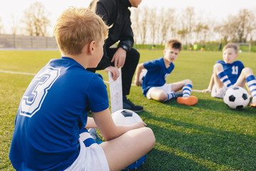 Young Soccer Trainer Coach Explaining Tactic on Team Sports Tactics Board. Children During Soccer Football Coaching Session. Boys in Soccer Team Listening to Coach