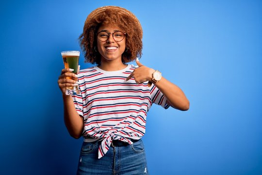 Young beautiful African American afro woman with curly hair on vacation drinking glass of beer with surprise face pointing finger to himself