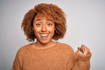 Young beautiful African American afro woman with curly hair wearing casual sweater screaming proud...