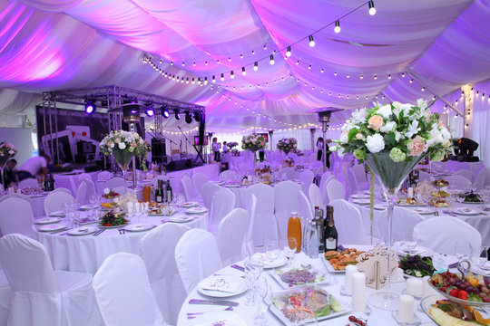 Wedding hall without guests with white chairs and decor in the outdoor wedding tent