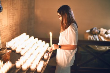 Young beautiful woman turning on candles at church