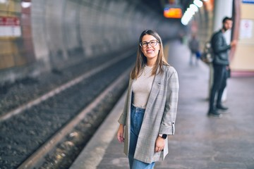 Young beautiful woman smiling happy and confident. Standing with smile on face at platform of train...