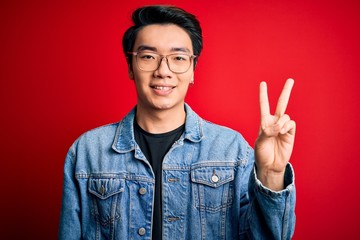 Young handsome chinese man wearing denim jacket and glasses over red background showing and pointing up with fingers number two while smiling confident and happy.