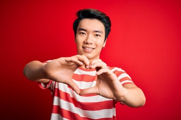 Young handsome chinese man wearing casual striped t-shirt standing over red background smiling in love doing heart symbol shape with hands. Romantic concept.