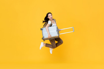 Excited beautiful Asian woman tourist jumping with luggage