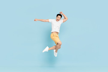 Happy handsome Asian man smiling and jumping