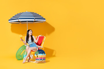 Surprised beautiful Asian woman sitting on beach chair