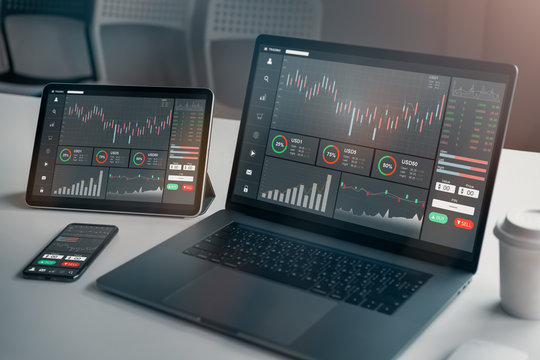 Stock exchange market concept, laptop and tablet, smartphone on the table with graphs analysis candle line in office room, diagrams on screen.