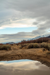 California valley view with snowy Sierra Nevada mountain range reflected in rain puddle in dirt road