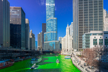 Papiers peints Chicago Chicago building and cityscape on Saint Patrick's day around Chicago river walk with green color dyeing river in Chicago Downtown, illinois, USA, crowned irish and american people are celebrating.
