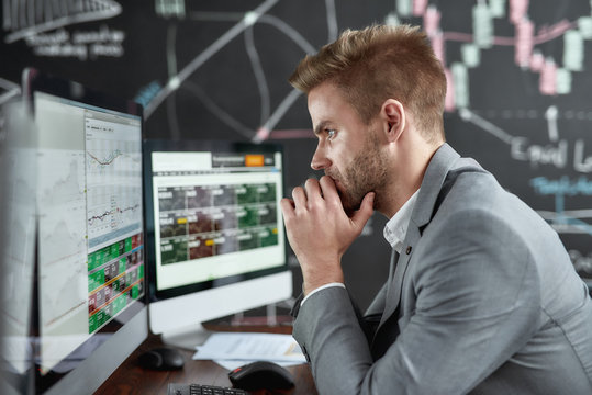 Keep growing with smart ideas. Portrait of successful young trader looking focused while sitting in front of multiple monitors in the office. Blackboard full of chart and data analyses in background.