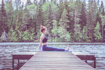 Young yogi  girl  practicing yoga, sitting in Staff exercise, Dandasana pose on the lake. The concept of appeasement,  healthy lifestyle.