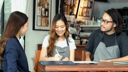 Asian woman sign corporate contract, Asia small business ower and partner sign contract with bank adviser agent at coffee shop