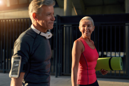 Sport making us happy. Active middle-aged couple in sports clothing smiling and talking about something while going to exercise together outdoors. Fitness couple