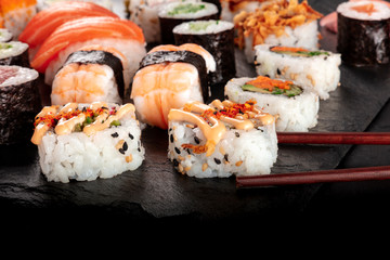 Large sushi set, close-up with chopsticks and copy space on a black background. An assortment of...