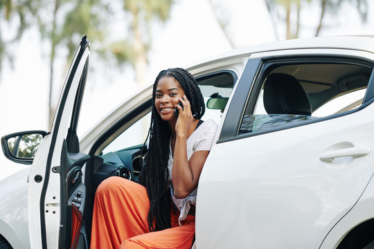 Attractive young Black woman sitting in car and talking on phone with friend or boyfriend