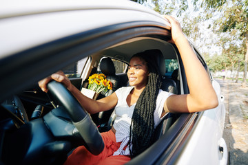 Beautiful young woman with long braided hair wnjoying driving her car