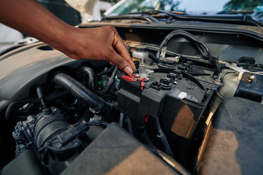 Close-up image of woman checking or changing car battery