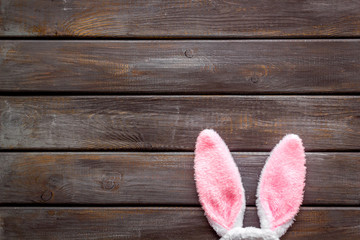 Easter bunny's ears on dark wooden background top-down copy space