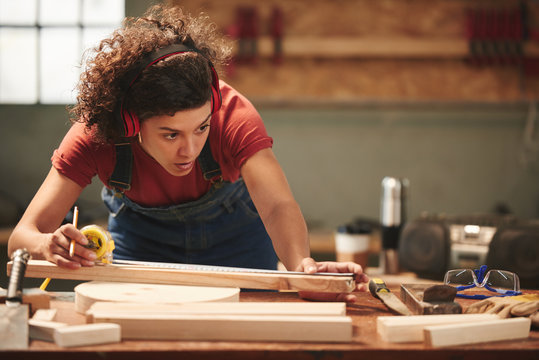 Young concentrated curly woman in ear defenders and overall measuring wooden plank with tape measure
