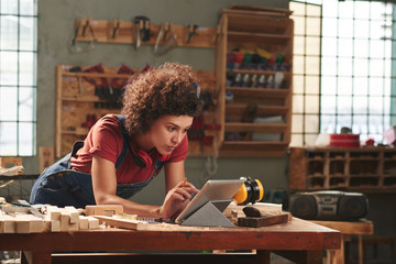Fototapeta Young concentrated woman with curly hair reading instructions on digital tablet before working with wood obraz