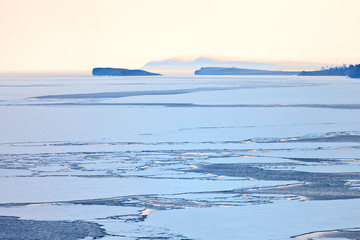 Baikal Lake in spring time. Ice drift in the Small Sea Strait in foggy and snowy weather at sunset. Beautiful cold natural background
