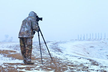 Lake Baikal in bad weather. Olkhon island in spring snowfall. Blurred silhouette of a tourist in snowy hiking suit with camera on tripod during filming (the camera and tourist's face are out of focus)