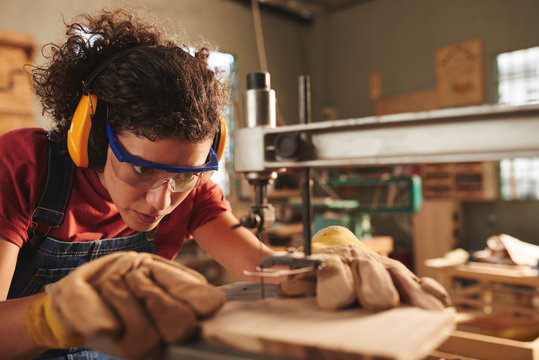 Close-up view of young concentrated female carpenter in safety glasses and ear defenders drilling hole in wooden plank with drill press