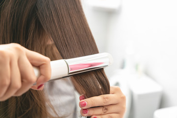 Close up Hair iron straightening beauty care in dressing room.