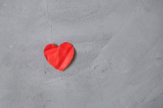 crumpled paper heart on the concrete floor.  Broken relationships in bad Valentine's day. concept.