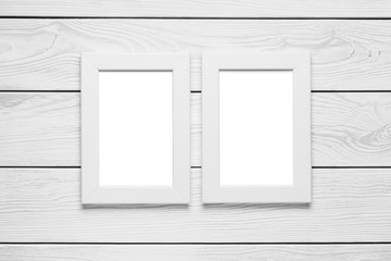 Two white empty frames hanging on the white wooden wall