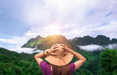 Traveler woman standing on top of cliff in mountains at sunset and enjoying view of nature landscape views,copy space.