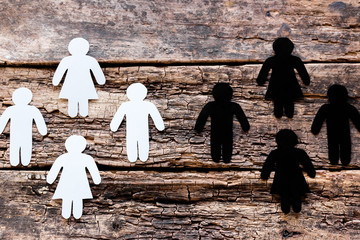 group of white and black silhouettes against each other on a wooden background. stop racism concept