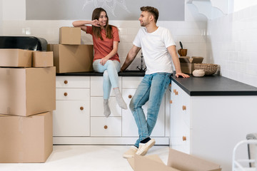 Young couple with cardboard boxes moving in new house