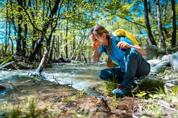 Fototapeta Woman refreshing herself with fresh water from creek while hiking obraz