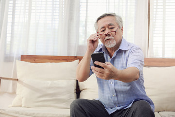 Older men move glasses down to look at the phone in the hand due to Hyperopia problems, which makes vision difficult.Health problems of the elderly.