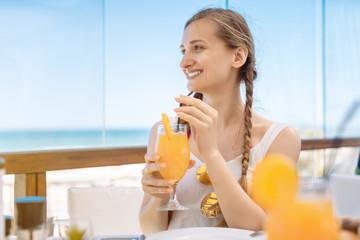 Beautiful woman in vacation enjoying orange juice in beach restaurant
