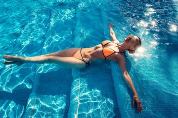 Beautiful woman relaxing in swimming pool of resort or hotel