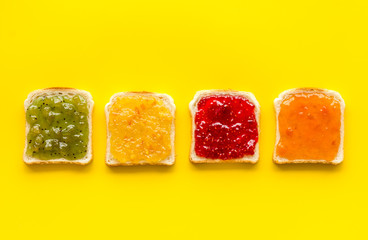 Toast with jam. Colorful set on yellow background top-down copy space