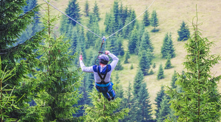 Descent from the mountain on a metal cable. Zipline is an extreme kind of fun in nature_