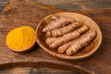 A wooden bowl with curcuma powder and a bowl with whole turmeric roots on a wooden cutting board.
