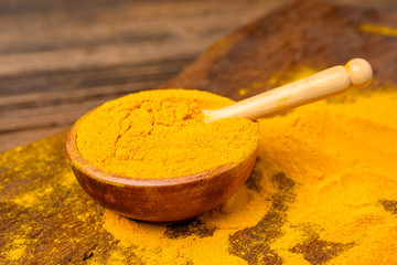 Dried curcuma powder in a wooden bowl with a wooden spoon in front of a wooden background.