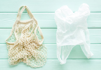 Zero waste concept. Textile and plastic bag on green wooden background top-down