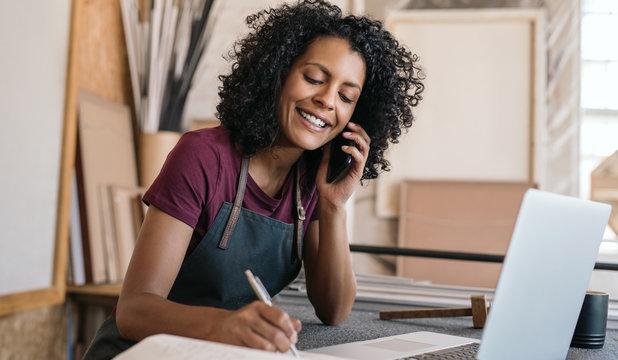 Smiling entrepreneur talking on the phone in her framing studio