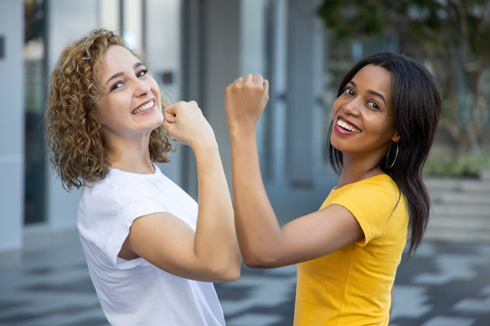 confident caucasian woman and african woman working together; concept of skin color tolerance, world peace, ethnicity understanding, good strong team, confident teamwork
