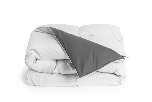 Folded soft white duvet, blanket or bedspread with the gray back side and empty white label, against white background. Close up photo